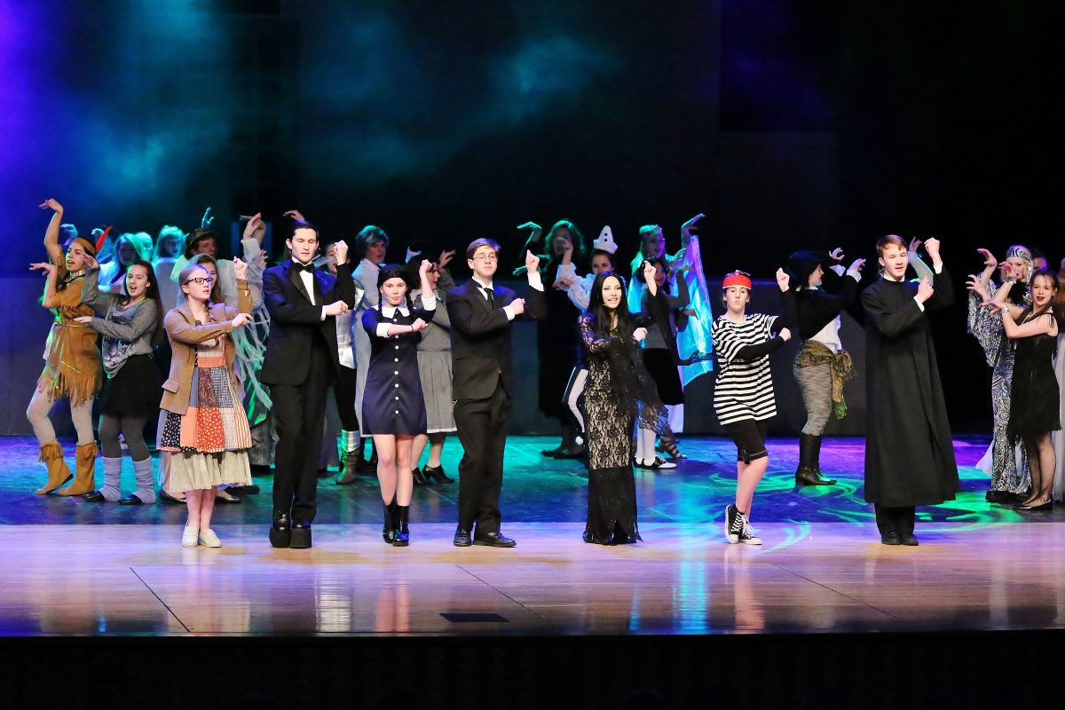 cast of the Addams Family dancing on stage